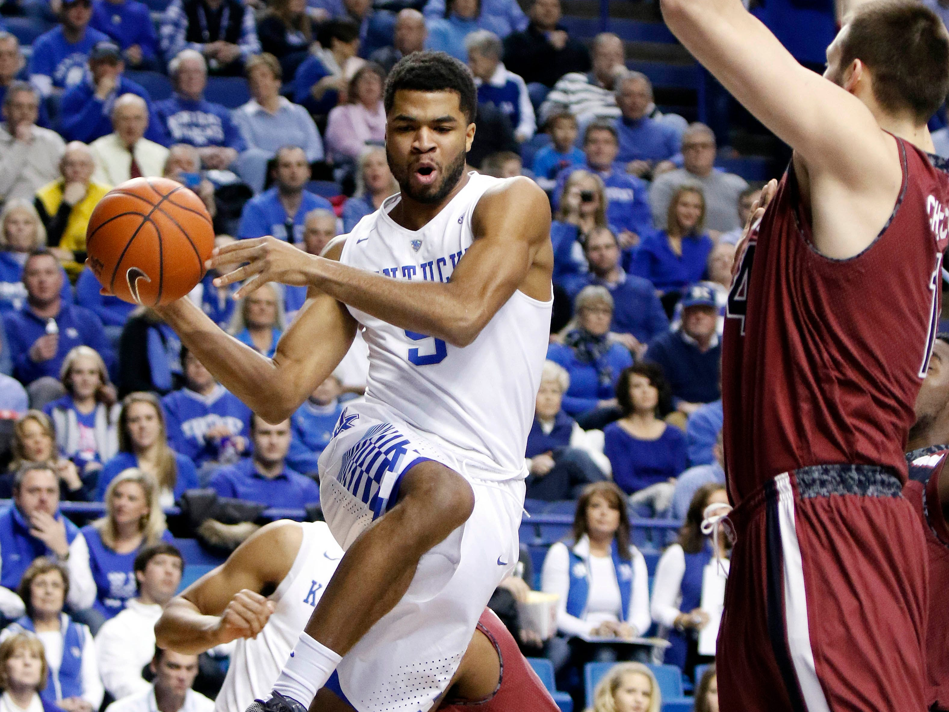 Kentucky's Andrew Harrison, left, passes around South Carolina's Laimonas Chatkevicius during the first half of an NCAA college basketball game, Saturday, Feb. 14, 2015, in Lexington, Ky. (AP Photo/James Crisp)