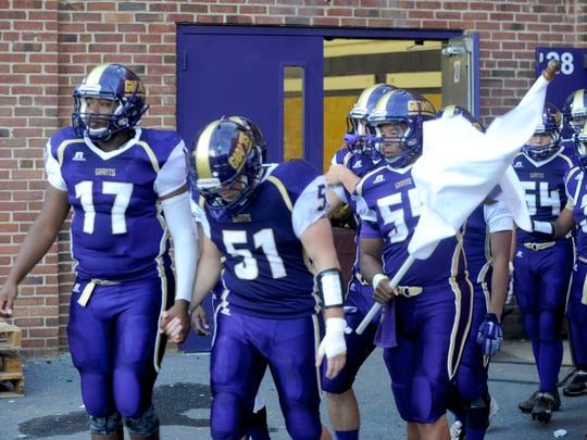 Players hold hands as they walk out to the field on Friday. The Little Giants beat Spotswood, 34-21.