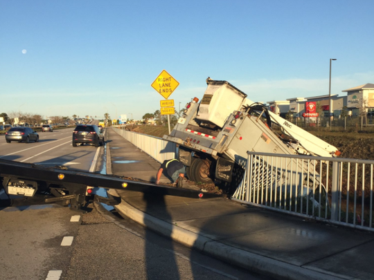 A truck was left hanging over the edge of a drainage canal Tuesday after a crash on Palm Bay Road.