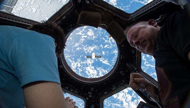 """Expedition 42 Commander and NASA Astronaut Barry """"Butch"""" Wilmore, with the assistance of Flight Engineer of the European Space Agency Astronaut Samantha Cristoforetti, prepared to use the Canadarm2 robotic arm to grapple the SpaceX Dragon (CRS-5) ship on Jan. 12 2015."""