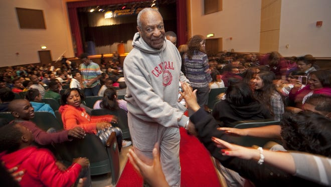 Bill Cosby shakes hands while leaving the auditorium at A.I. DuPont Middle School in 2011 after speaking to students.