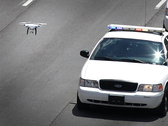 A drone follows the slow procession of police vehicles heading north on Delaware Street from Downtown Indianapolis in route to Crown Hill Cemetery for the burial of Indianapolis Metropolitan Police Department officer Perry Renn on July 11, 2014.