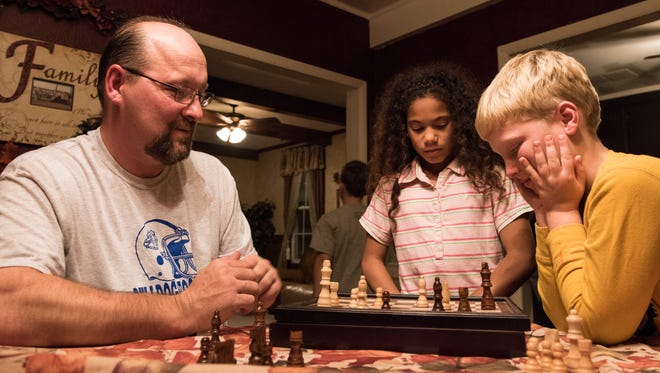Scott Ness plays a game of chess with Brad, 9, while Destiny, 10, watches at their Hebron home on Thursday, Nov. 20, 2015.