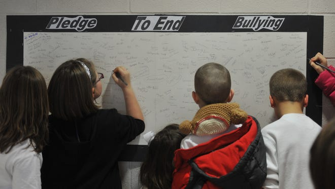 Centerville-Abington Elementary School students sign an anti-bullying pledge.