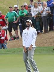 Adam Hadwin flips his putter into the air after missing