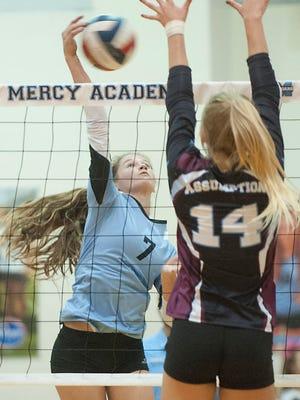 Mercy setter Elena Scott tries to return the ball as Assumption outside hitter Anna Debeer puts up her hands in defense. Assumption beat Mercy 26-24, 25-15 and 25-17 to retain their #1 state standings against #2 Mercy.02 September 2017