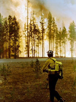Larry Walters, a U.S. Forest Service firefighter from Higgins, Miss., watches the North Fork fire burn in the Yellowstone National Forest on Aug. 24, 1988.