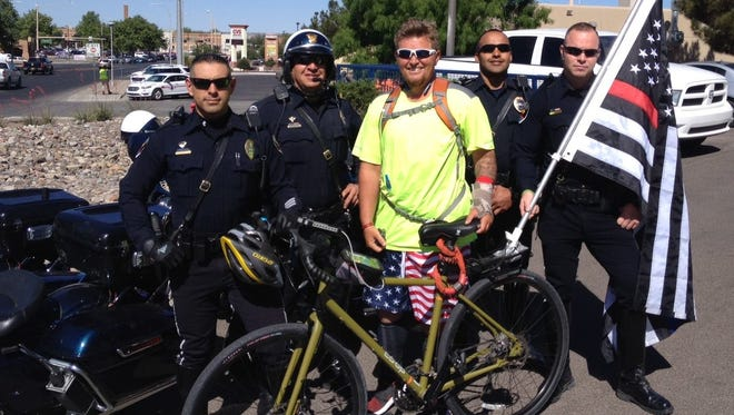Aodhan O'Ferrell, a former firefighter in California, visits with Las Cruces police officers, while on a cross-country trip to raise awareness for motorists to 'move over for emergency vehicles.'
