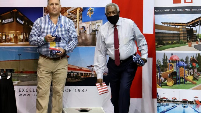 Adam Shelton with Hydco General Contractors and Construction Management, left, throws a game of cornhole with Mayor George McGill, Thursday, September 3, during the Arkansas Recreation & Parks Association Conference and Trade Show at the Fort Smith Convention Center. Scheduled through September 4, the event features Chris Nunes, CPRE, Director of Parks and Recreation for The Woodlands Township, in The Woodlands, Texas and is the first vendor booth conference since March 15, 2020, due to the COVID-19 pandemic.