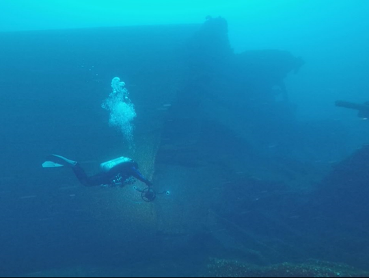 Technical diver riding a dive propulsion vehicle near