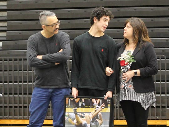 Willard wrestler Niko Chavez (center) converses with his parents, Jeffrey and Sani Chavez, during wrestling senior night ceremonies at Willard High School, Jan. 31, 2017.