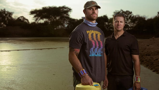 St. Louis Rams' Chris Long and Doug Pitt, Springfield businessman and philanthropist, stand next to a pond in Tanzania where locals get drinking water. Long came up with the Waterboys Initiative to raise money to build water wells for impoverished communities in East Africa.