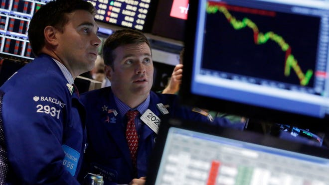 Specialists Robert Tuccillo, left, and Frank Masiello work on the floor of the New York Stock Exchange. The Dow Jones industrial average plummeted as much as 460 points in afternoon trading, then clawed back much of the ground it lost.