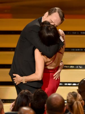 Julia Louis-Dreyfus wins Outstanding Lead Actress in a Comedy Series for 'Veep' and kisses Bryan Cranston onstage at the 66th Annual Primetime Emmy Awards held at Nokia Theatre L.A. Live on August 25, 2014 in Los Angeles, California.