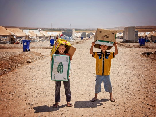 Two boys make a game of playing with cardboard boxes