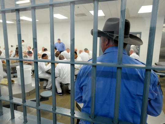 A corrections officer watches as inmates eat lunch at the Department of Correction North Central Unit near Calico Rock in 2014. Prison overcrowding was a major issue when the state legislature convened the following year.
