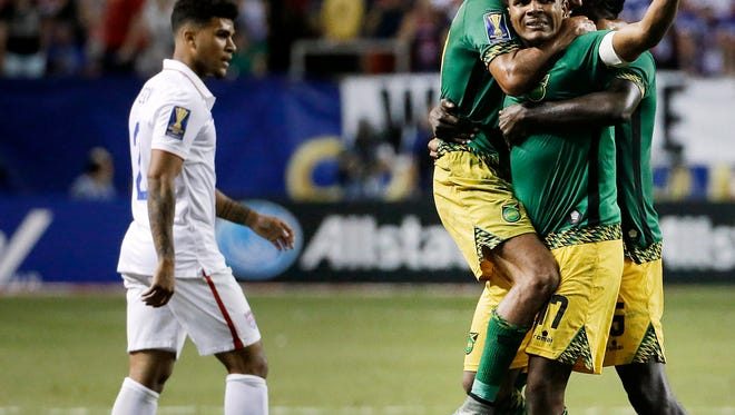 Jamaica's Rudolph Austin, facing camera, celebrates with teammates Joel McAnuff, left, and Je-Vaughn Watson, right, as United States' DeAndre Yedlin walks off the pitch after Jamaica defeated the United States 2-1 in a CONCACAF Gold Cup soccer semifinal Wednesday in Atlanta.