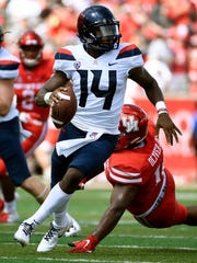 Arizona quarterback Khalil Tate escapes a tackle against Houston on Saturday.