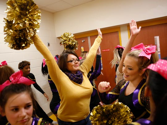 Waynesboro head coach Rebecca Stanley raises her arms to high five her athletes before the start of the Conference 29 competition cheer championship at Fluvanna County High School on Saturday, Oct. 24, 2015.