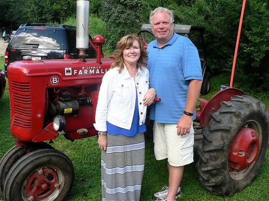 "Pictured with Catherine's Farmall 'B"" (her 4-wheeler) are her daughter, Sally, and husband, Chuck Walker, who own the 40 acres containing the farmstead."