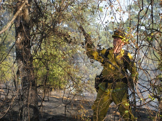 A Redding firefighter works to put out a fire that