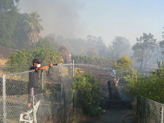 A resident off Rosewood Drive aims a hose on a fire