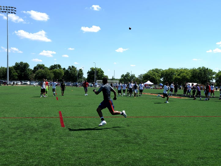 High school football students run drills on the newly