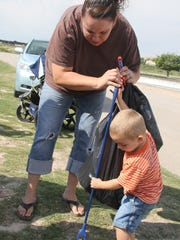 Heather Kunsky helps her son Mason, 2 1/2, pick up
