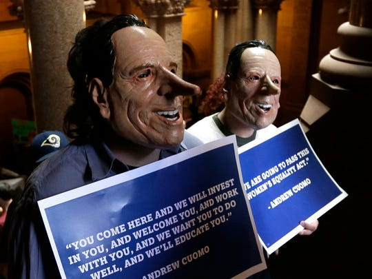 Demonstrators wearing masks resembling Gov. Andrew Cuomo rally against the proposed state budget outside at the Capitol on Monday.