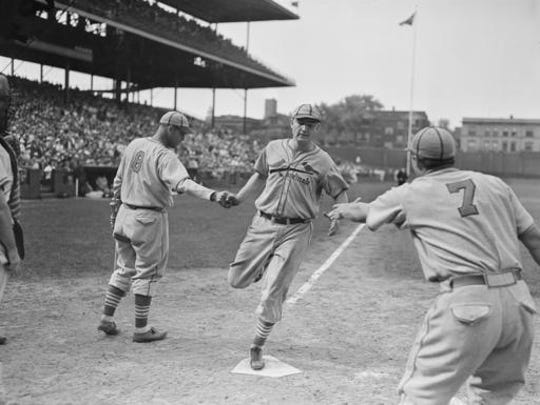 FILE - In this Aug. 4, 1936 file photo, Johnny Mize's is congratulated after his home run in the 8th inning with two mates aboard, clinched the Cardinals' victory over the Cubs, 6-1, in Chicago. Mize is shown scoring and being greeted by teammates Joe Medwick (7) and Spud Davis (8). The Abraham Lincoln Presidential Museum plans to unveil an exhibit chronicling the history of the rivalry between the Chicago Cubs and the St. Louis Cardinals opens March 24, 2017 in Springfield, Ill.