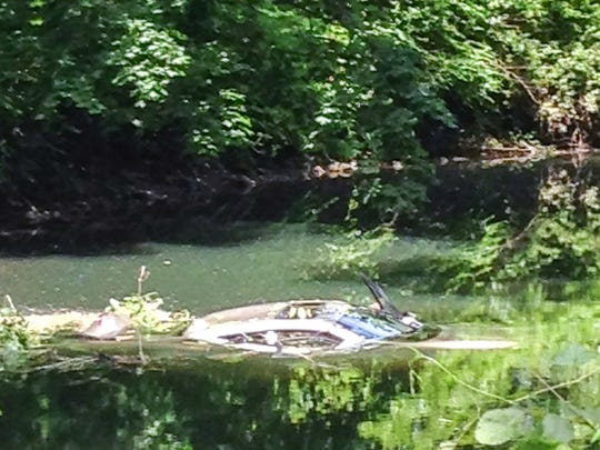 A four-door Honda in the Bronx River in Eastchester after passersby pulled two people out.