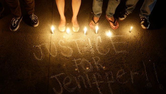 """Protesters stand next to a scribbled message during a protest to demand justice in the killing of Jeffrey """"Jennifer"""" Laude."""