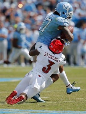 Louisville's Conrelius Sturghill wraps up North Carolina's Anthony Ratliff-Williams following a catch in the second half. Sept. 9, 2017