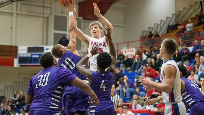 Jay County's Ryan Schlechty attempts a shot while Central moves to block. Jay County won 54-47 Friday night in overtime.