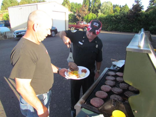 Aumsville Fire Maintenance Officer Steve Busby serves up a double stack as burgers were a preferred fare at the popular Shaw Fire Station during National Night Out Tuesday, Aug. 4, 2015.