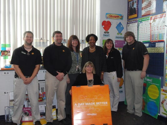 """Elizabeth Ness, front, a kindergarten teacher at Ferguson Elementary School, recently won $1,000 worth of supplies in the Office Max """"A Day Made Better"""" campaign. Behind her are Sarah Baker, Ferguson principal, and Deborah Wortham, district superintendent, along with Office Max staff."""