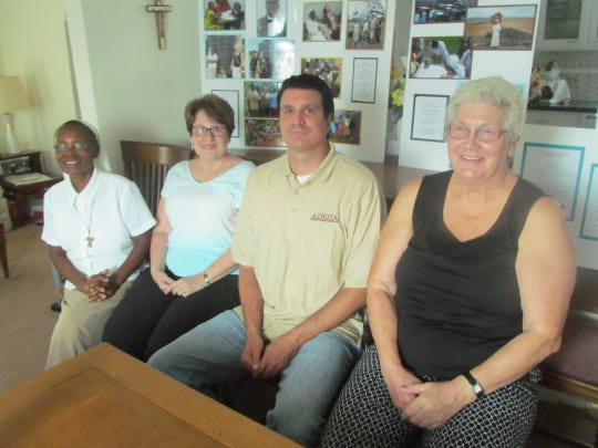 From left, Sister Anisia Muthoni, Marlene Hutcheson, Anthony Paniccia and Rozann Greco are helping raise money to build a boarding school in Komarock, Kenya. Behind them are pictures of the project.
