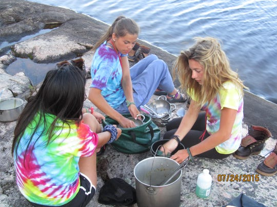Day 8: Kylee Brimsek, Autumn Albers and Keely Bauerly wash dishes after dinner.