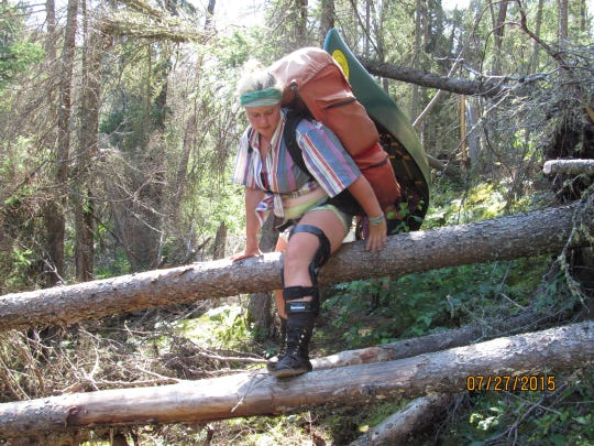 Day 11: Hannah Windschitl climbs over fallen trees on a portage around two sets of rapids on Irwin Creek.