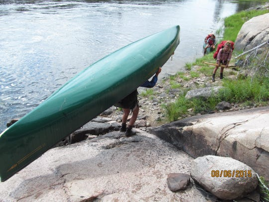 Day 21: Keely Bauerly and Cyndi Cao wait as Autumn Albers descends a slippery rock face while portaging the canoe.