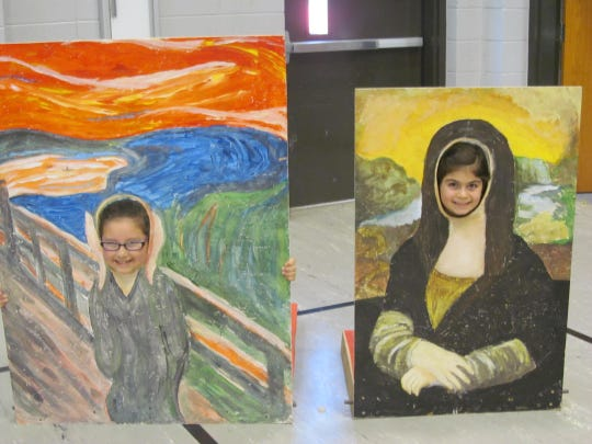 """Northwood High School second-graders Isabella Neal (left) and Morgan Daigle (right) become the art at a school-wide student art show in Lena on Tuesday. Students at the school cut and built the easles out of donated wood from Boise Cascade. Art teacher Amy Milliner painted them to look like Edvard Munch's """"The Scream"""" and Vincent van Gogh's """"Mona Lisa"""" without faces."""