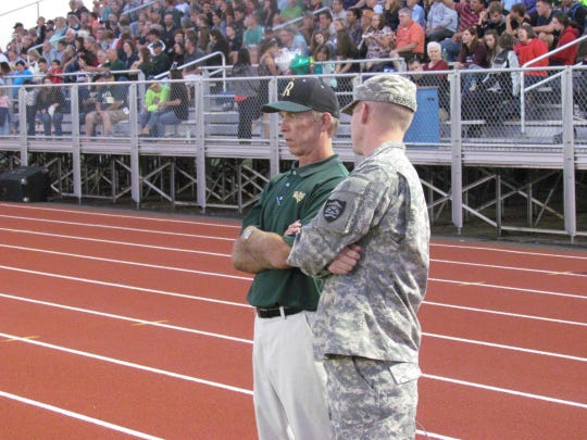 Regis High School Athletic Director Don Heuberger (left) and his son Joe chat on the sidelines during the school's head to head tilt with Portland Christian, a Homecoming and 50-year anniversary celebration football game Friday, Sept. 13, 2013.