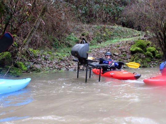 Kayakers paddle down a stream surrounded by private land. They came across a grill floating in the middle of the stream.
