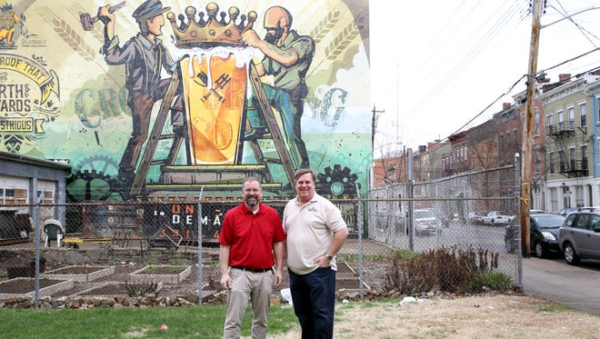 Steve Hampton, left, executive director of The Brewery District Community Urban Redevelopment Corporation (BDCURC) and Greg Hardman, president of the board of trustees of The Brewery District and owner of Christian Moerlein Brewing Company, stand near the mural Artworks created last summer on McMicken Ave. that will be part of the Cincinnati Brewing Heritage Trail.