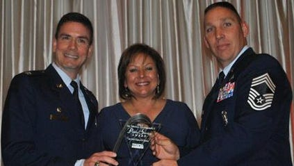 Col. Paul W. Tibbets IV, Air Force Inspection Agency commander, left, and Chief Master Sgt. David McBride, AFIA's chief enlisted manager, right, accept the New Mexico Distinguished Public Service Award from Governor Susana Martinez, center, at the 43rd annual NMDPSA banquet Nov. 1, 2012, in Albuquerque.