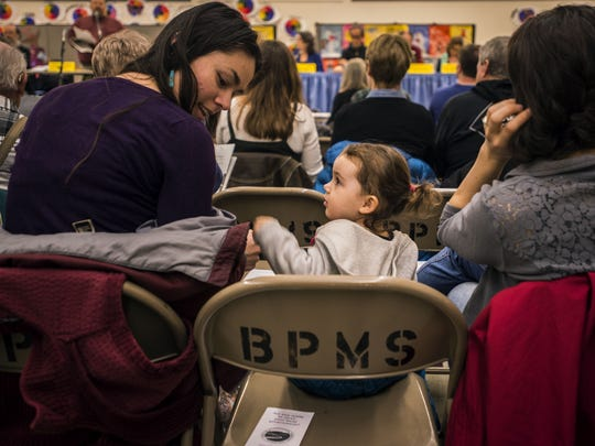 Everleigh Heir, 1 1/2, the fourth generation to attend Town Meeting Day in Huntington, turns to her aunt, Jane Keir while her mom Miranda listens to opening statements by the select board on Tuesday, March 7, 2017, at Brewster-Pierce Memorial School.