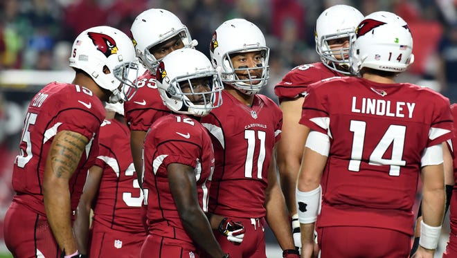 Larry Fitzgerald (11) joins the Cardinals huddle during the game against the Seattle Seahawks on Dec. 21, 2014 in Glendale.