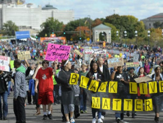 """About 100 supporters of the """"Black Lives Matter"""" march along the rout of the Medtronic Twin Cities Marathon, in St. Paul, Sunday, Oct. 4 2015. The group marched within 50 yards of barriers near the end of the course but did not disrupt the event. St. Paul police say no one was arrested. (Photo by AP Photo/Craig Lassig)"""