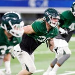 Michigan State linebacker Riley Bullough, center, runs a drill with teammates during a practice for the NCAA Cotton Bowl college football game against Alabama at AT&T Stadium Sunday in Arlington, Texas.