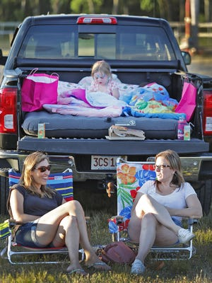 Moms Tracey Westervelt of Hingham and Chrissie Beatty of Scituate enjoy the sunset as daughters Leila, 5 and Ava, 4 play in the back of the pick up with their blankets and toys.    The pop up Marshfield Drive in at the Marshfield Fairgrounds opened to a sold out showing of Trolls World Tour on Thursday June 24,  2020.
